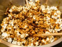 Mixing Popcorn, Nuts & Caramel Syrup in a Bowl