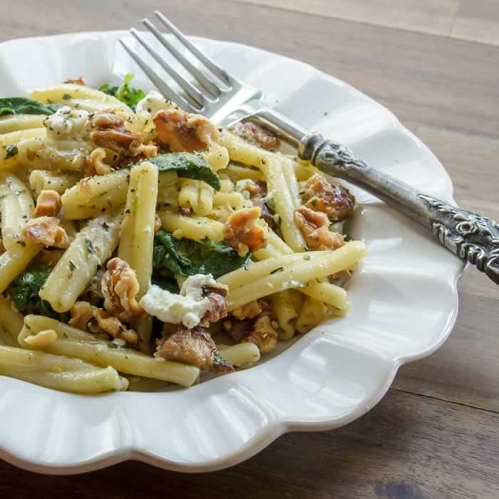 Strozzapreti Pasta with Fava Bean Greens Pesto, Spicy Italian Sausage & Toasted Walnuts